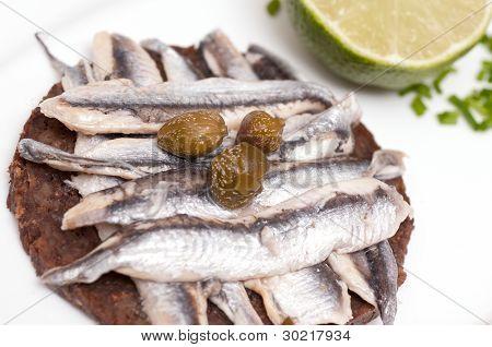Canape de pan de granero con sardinas y alcaparras