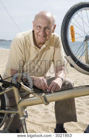 Senior Man Repairing His Bike