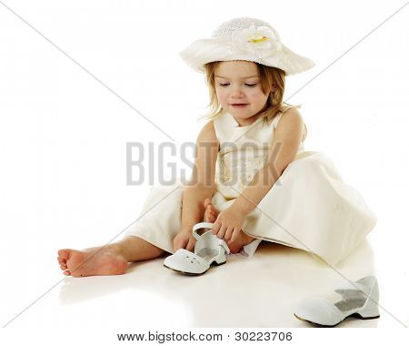 An adorable 2 year-old in dressy white clothes putting on her own shoes.  On a white background.