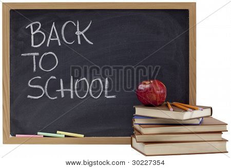 back to school concept - white chalk handwriting on blackboard, stack of old books, red apple and yellow pencils
