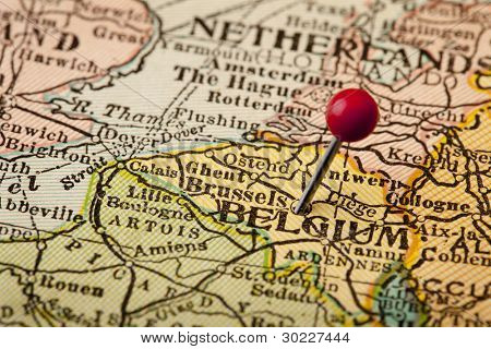 Belgium and Brussels (European Union Center) on vintage 1920s map with a red pushpin, selective focus