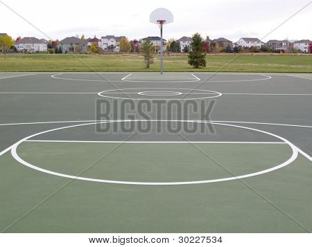 green recreational basketball court in a park with houses in background