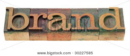 brand word in vintage wooden letterpress printing blocks, stained by color inks, isolated on white