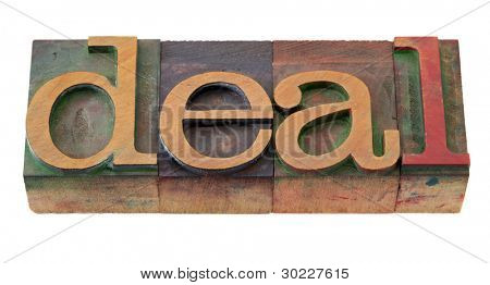 deal - word in vintage wooden letterpress printing blocks, stained by color inks, isolated on white