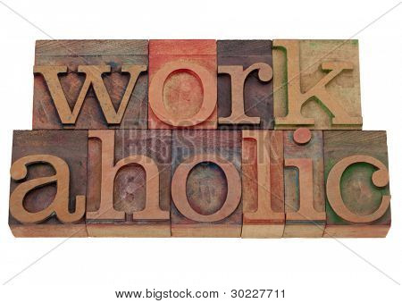 a compulsive worker concept, workaholic word in vintage wooden letterpress printing blocks, stained by color inks, isolated on white