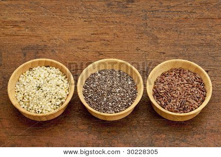 chia, flax and hemp healthy seeds in small wooden bowls