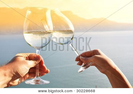 Two hands holding wineglases against vineyards in Lavaux region, Switzerland