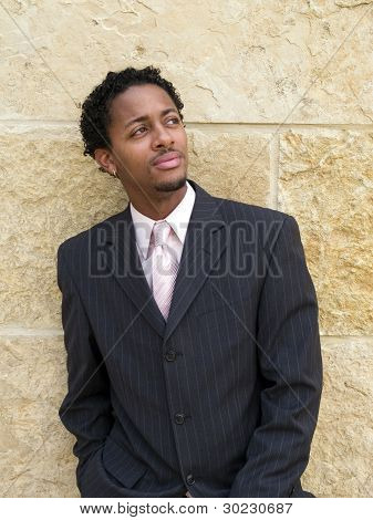 Businessman leaning on wall