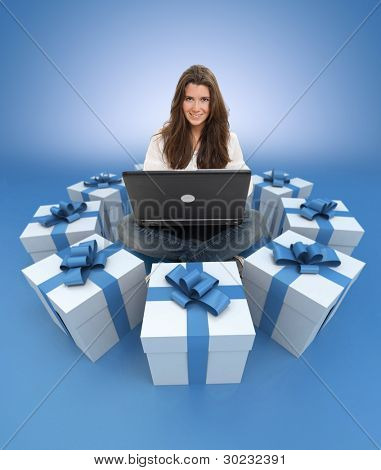 Young girl sitting with a laptop surrounded by gift boxes