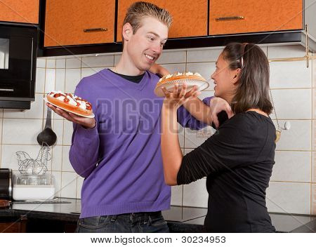 Young couple starting a fight with cream pies in the kitchen