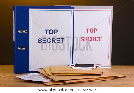 Envelopes and folders with top secret stamp and photo papers with CD disks on wooden table on brown background