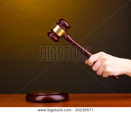 Judge's gavel in hand on brown background