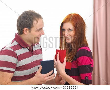 Happy Young Couple Exchanging Presents