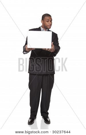 African American Businessman Looking Warily At Laptop Computer
