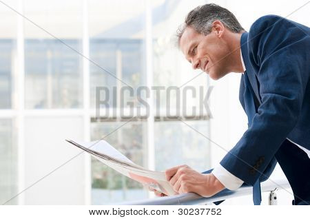 Mature businessman looking and reading newspaper in a modern office
