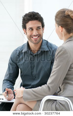 Smiling business man talking with his colleague during an informal meeting at office