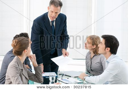 Mature businessman talking and explaining his business strategy to his colleagues at office