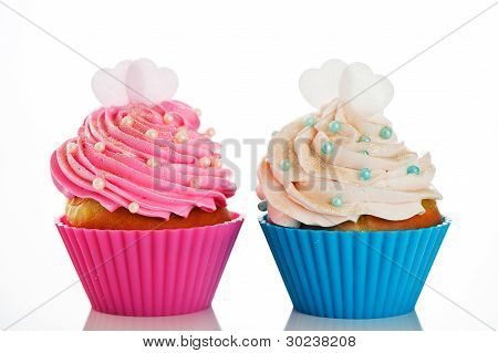 Two Cupcakes In A Pink And Blue Baking Cups With Pink And White Cream, With Decoration And Two Heart