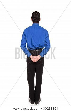 Businessman Standing With Hands Clasped Behind His Back