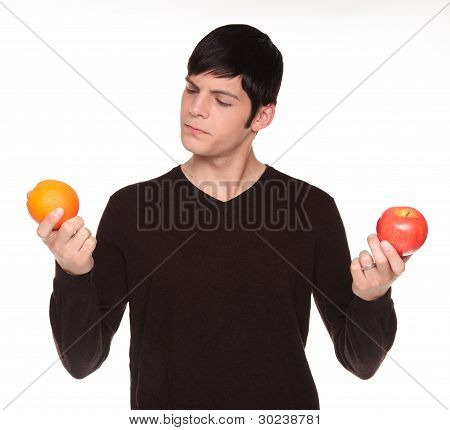 Caucasian Man Comparing Apple To Orange