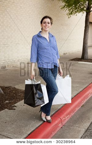 Pretty Woman In Blue Jeans Standing With Shopping Bags At Mall