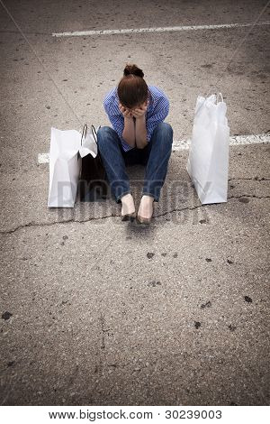 Lost Woman Sitting In Parking Lot With Shopping Bags Covering Face