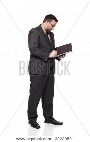 Side View Of Caucasian Businessman Writing On Notepad.