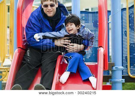 Padre va abajo Deslice con hijo discapacitado que tiene Parálisis Cerebral