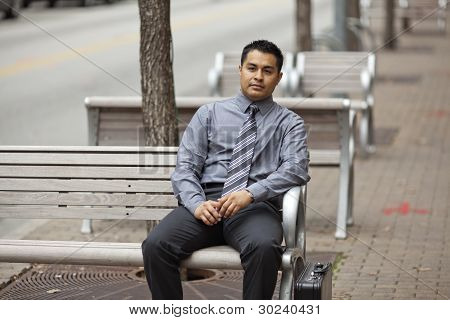 Hispanic Businessman - Sitting On Bench With Briefcase