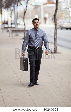 Empresário hispânico - centro andando com maleta
