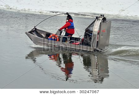 Airboat on the river in the winter time. Two guards inside.
