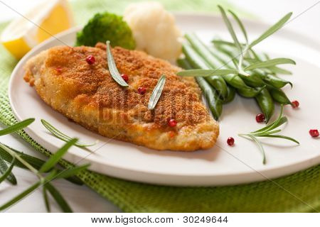 Breaded fish fillet with vegetables and rosemary
