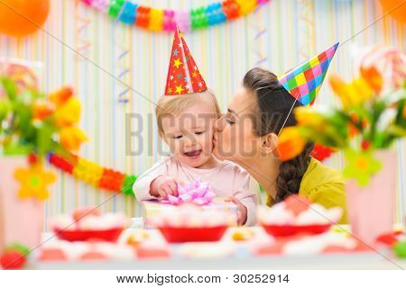 Mother Kissing Her Happy While Baby Checking Present