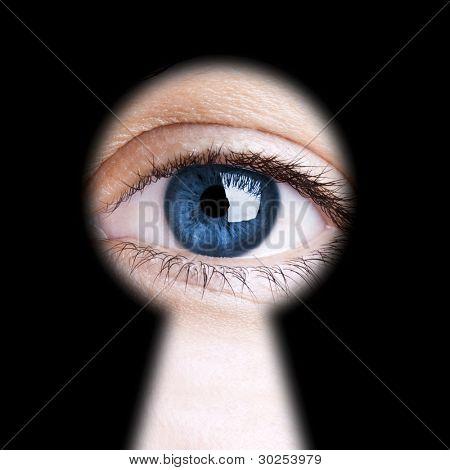 Eye looking through a blurred black keyhole