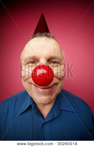 Portrait of a cheerful man with red nose smiling at camera on foolâ??s day