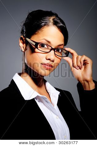 Confident Latino woman in suit touches her frames while posing for portrait