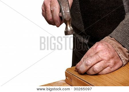 Close up of Old man hitting a nail onto a wooden beam