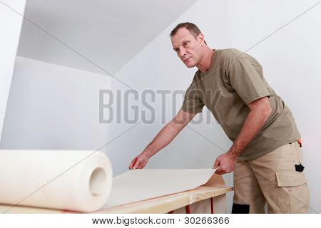 Man decorating apartment with new wallpaper