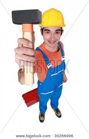 Young mason displaying lump hammer