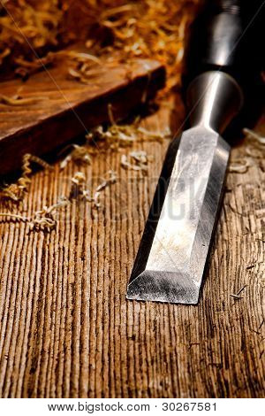 Wood Chisel On Distressed Old Wood Board Workbench