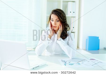Shocked business lady looking at the screen of laptop