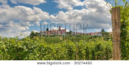 Panoramic view on beautiful vineyards and small town on the hill in Piedmont, Northern Italy.