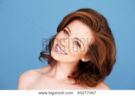 Redheadwoman with her head tilted to one side and a beautiful big smile