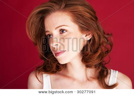 Beautiful redhead woman looking sieways with large wistful eyes.