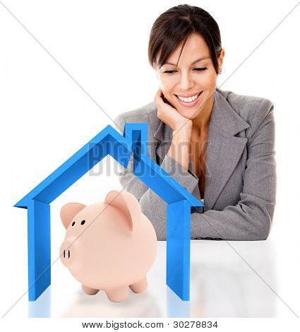 Business woman saving for a house in a piggybank - isolated over a white background