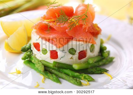 köstliche Vorspeise mit Lachs, Spargel und Hüttenkäse Creme auf weißen Teller.