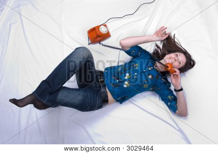 You And Me Talking With Each Other. Girl On The Red(Orange) Phone Lays On A Bed