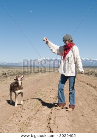 Woman And A Dog Playing