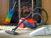 stock photo of cleaning house  - Two vacuum cleaners and a duster left by a fireplace - JPG