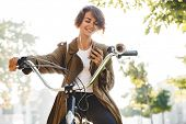 Image of a cute young amazing woman walking outdoors in park with bicycle beautiful spring day liste poster